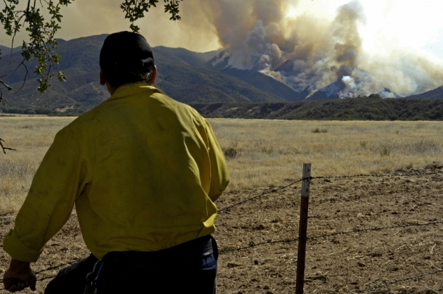 A firefighter looks on as the La Brea fire blazes through the hills of the Los Padres National Forest in 2009. The fire was started by equipment inside an illegal marijuana operation located in the forest. Credit: U.S. Air Force. Photo: Airman 1st Class