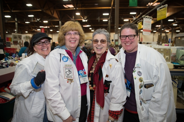 Four women in white coats smile at the camera inside the warehouse