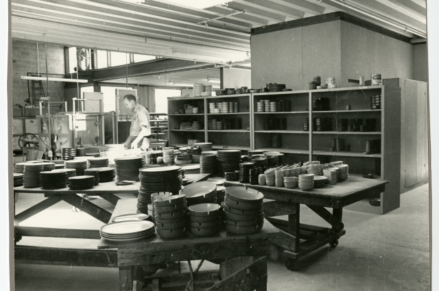 Black and white photo of the interior of Heath factory; worker in the mid ground near machinery; piles and shelves of ceramics throughout space