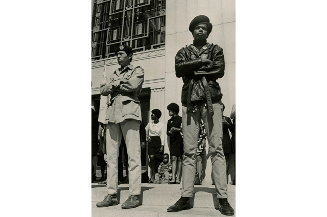Black and white image of two men standing in front of a courthouse with their arms closed