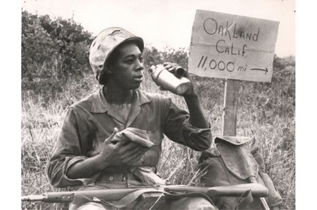 A black and white image of a Vietnam soldier holding a canteen in front of a sign that reads Oakland, Calif. 11,000 miles