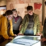 Adults look at maps inside the natural science gallery at OMCA in Oakland