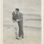 Black and white photo of Edith Heath and her husband kissing her on the cheek, on the beach shore