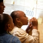Children write on comment board on wall