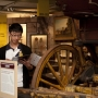 Man inspects booklet near antique covered wagon