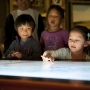 Group of children interact with interactive screen