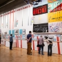 A group of people view a large timeline spanning an entire wall that denotes queer history in California
