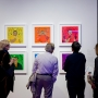 Four people view 6 colorful paintings hanging on the wall