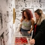 Two women smile as they look down at a checkerboard set inside a display case