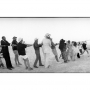 A black and white image of a large group of people pulling a rope to raise the first Burning Man sculpture