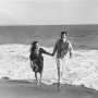 Black and white image of Charles and Ray Eames holding hands at the beach