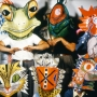 People wearing colorful masks of animals, namely a frog, insect, rooster, cat, and alligator