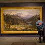 Man in jean jacket stands in front of large landscape painting