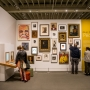 Wall of photos and paintings of varying sizes, visitors look at photos