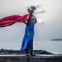Black child dressed up in a superhero costume and wearing VR headset