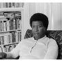 Photograph of author Octavia E. Butler sitting in a chair with books in the background