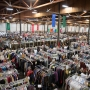 An overview of the large White Elephant Sale warehouse with large groups of people shopping in the many aisles