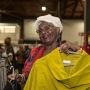 A woman smiles as she holds up a yellow sweater on a hanger