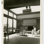 Black and white photo of Edith Heath in her home in living area with fireplace and skylight