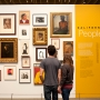 Couple stands in front of a wall of portraits