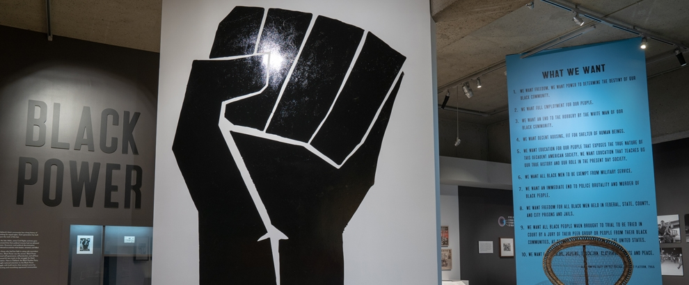 Black Power exhibition entrance with a large black fist on a white wall and the words: Black Power displayed on the wall behind it