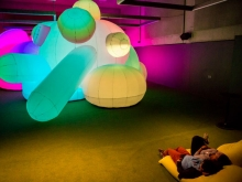 Museum visitors recline next to a glowing inflatable sculpture Nature's Gift at Oakland Museum of California