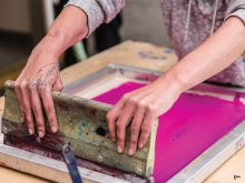Hands of a woman doing a dye transfer print process, holding a large tool at the end of a box of bright pink dye