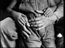 Black and white image of a grown man's hands and a small child's hands