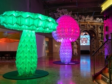 Two large, multicolored mushroom-shaped sculptures with a large golden archway in the background
