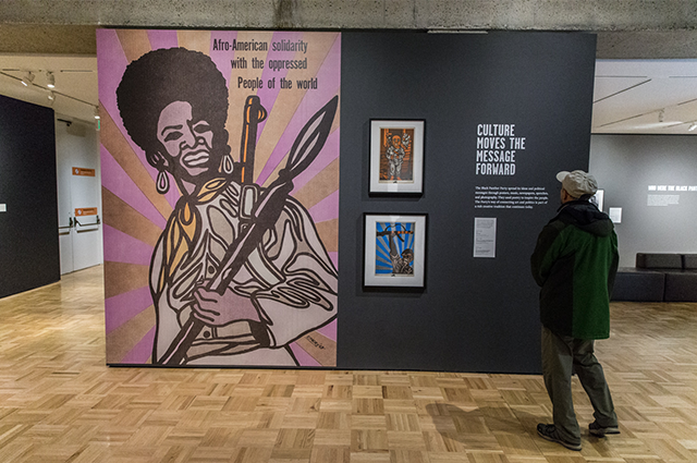 Rear view of a man looking at a piece from the Black Panther exhibit.