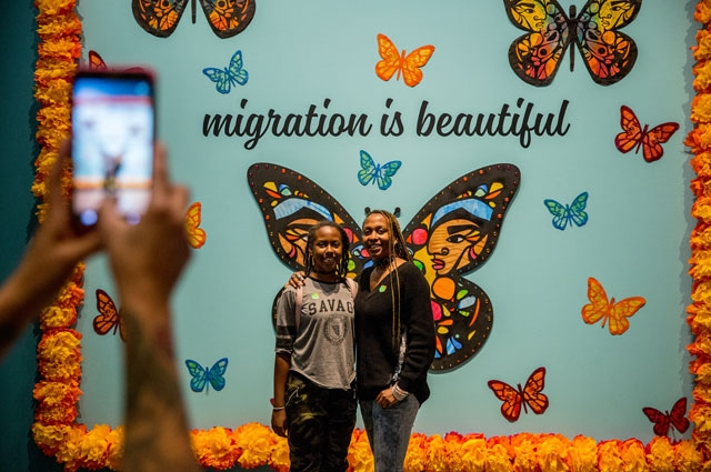 Museum visitors pose in front of Favianna Rodriguez's Migration Is Beautiful artwork at the Oakland Museum of California Days of the Dead exhibition.