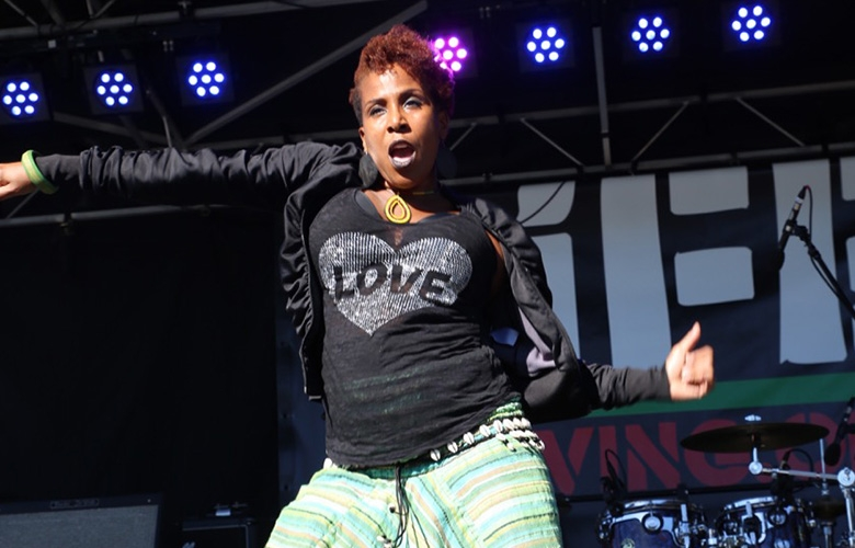 The dancer Traci Bartlow mid-movement on stage wearing a shirt with a heart