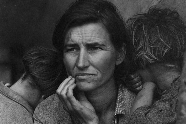 Black and white image of a mother with her hand to her face and two children embracing her