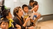 A teacher and students look up and point at something out of frame