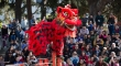 A large red Chinese dragon stands on stilts high above a large crowd of people
