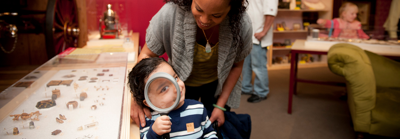 A small boy looks through a magnifying glass with his mother behind him