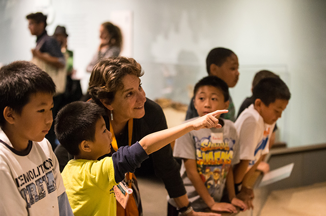 A child points and shows something to his teacher in one of the OMCA galleries.