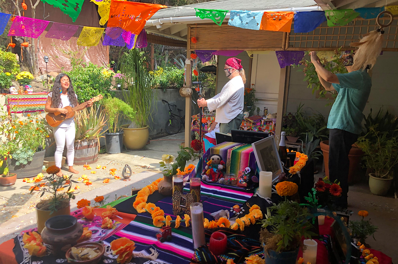A woman sings and plays the guitar in a backyard with a Dia de los Muertos altar while two people film her performance