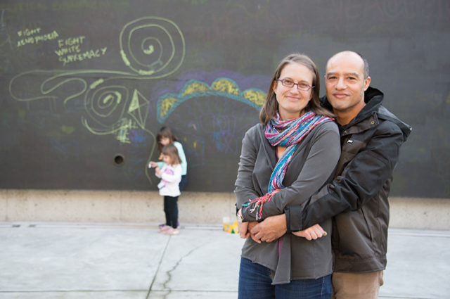 Alicia and Larry Van Riggs embrace in the foreground while their two young daughters draw on a large chalkboard in the background